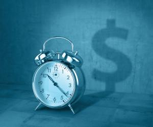 Alarm clock casting shadow of a dollar sign